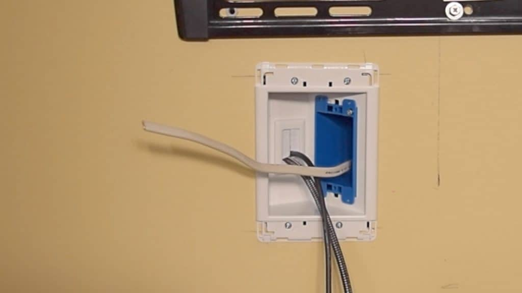 Setting outlet box into larger opening of the recessed tv box